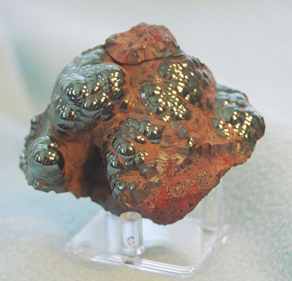 Haematite. When limonite is roasted, it turns partially to haematite and becomes more reddish.