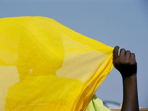 Malian Woman Photograph by Michael S. Lewis A woman in Diafarabe, Mali, holds her brilliant yellow scarf against a blue African sky. Her landlocked country is a desert land that was once a hub for ancient Saharan caravan routes.